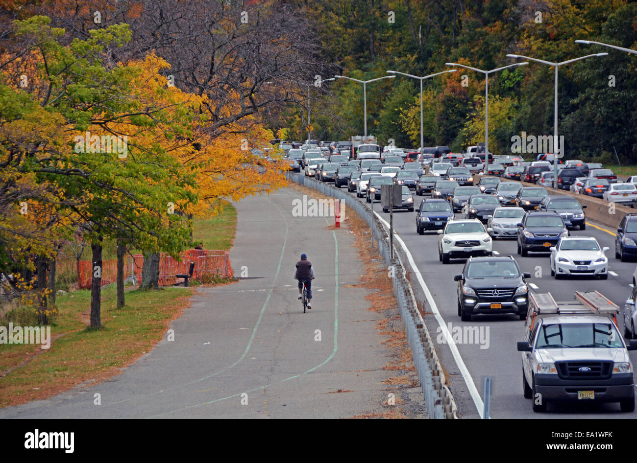 A man cycling near automobile traffic on an Autumn day near the Marina in Bayside, Queens, New York - Stock Image
