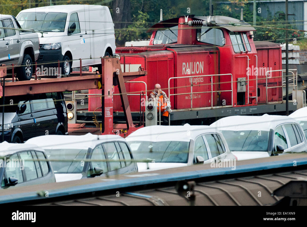 A staff member of the Deutsche Bahn (DB) climbs onto a diesel train engine between freight trains loaded with Volkswagen - Stock Image