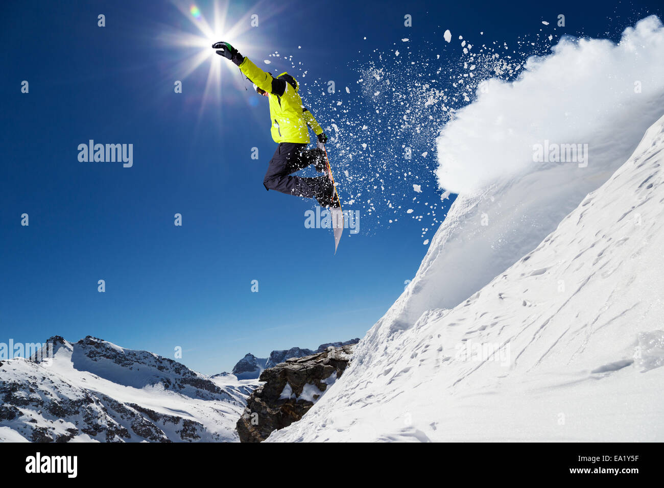 Alpine skier skiing downhill, blue sky on background - Stock Image