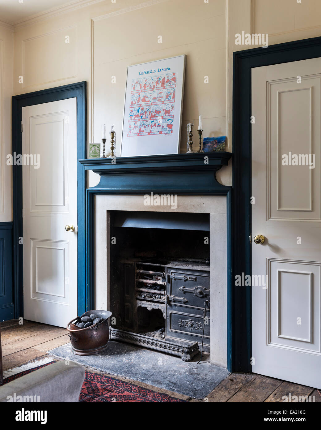 Signed Paul Brommer print above fireplace with original stove - Stock Image