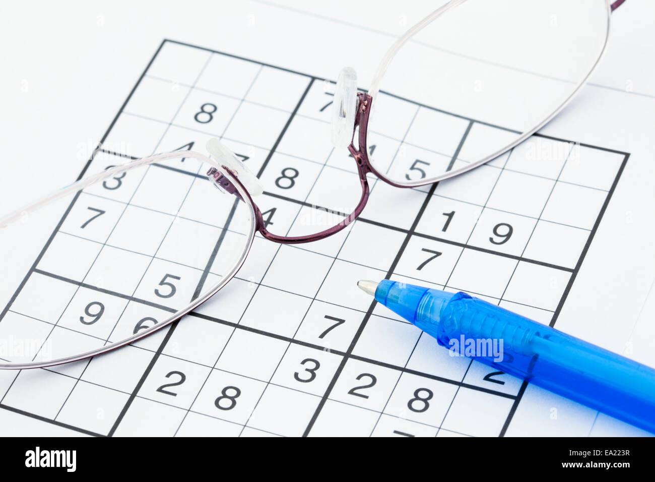 Suduko numbers puzzle spectacles and pen close-up to illustrate a mental health healthy mind concept. - Stock Image
