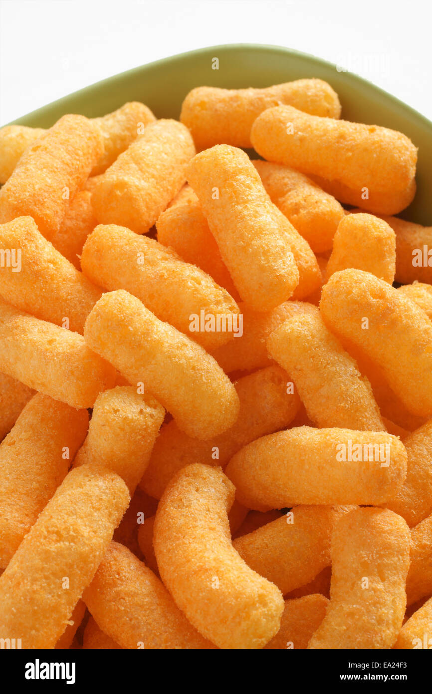 Bowl of cheese flavored puffed corn snacks - Stock Image