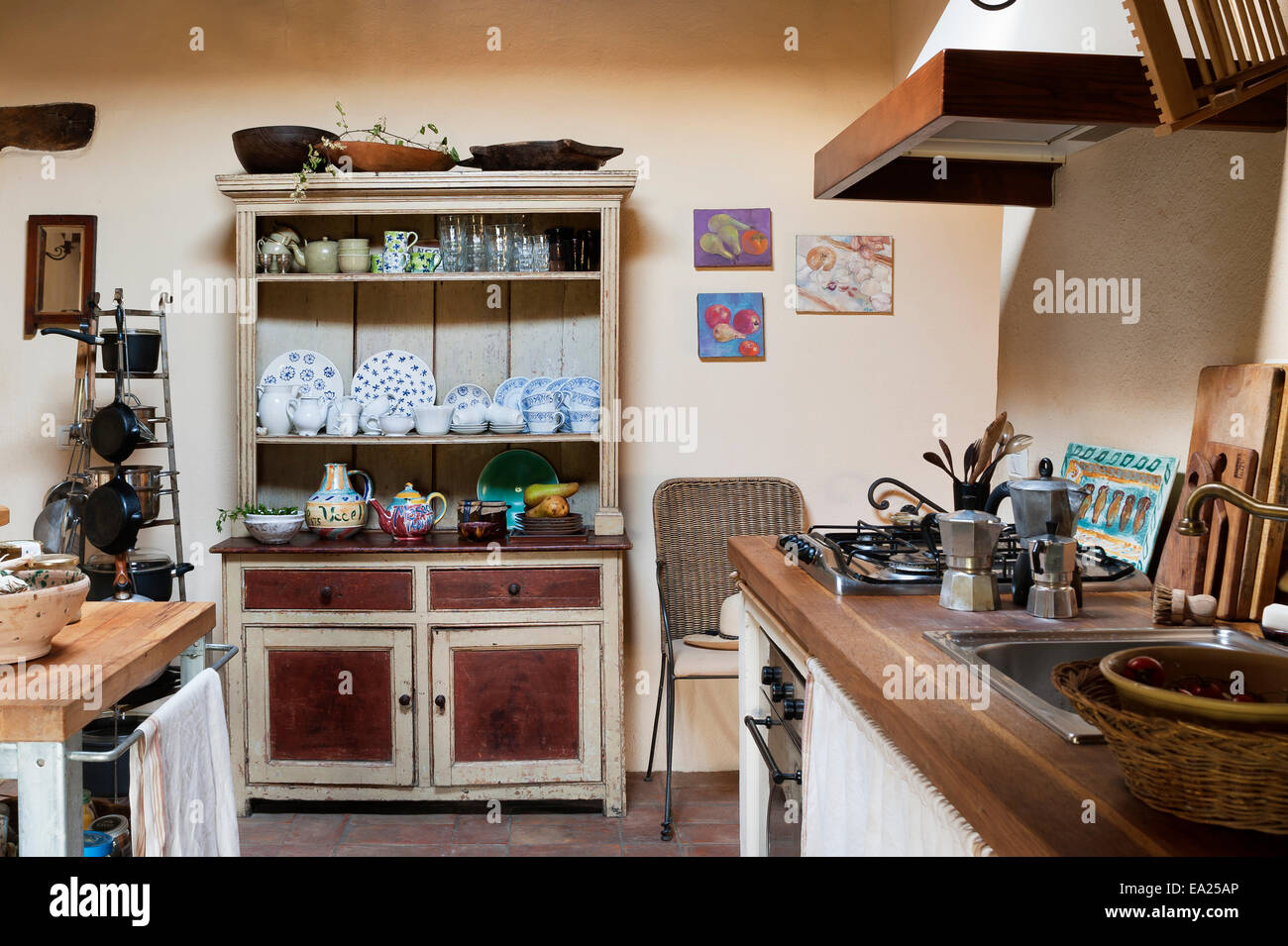Farmhouse style dresser in rustic country kitchen with decorative crockery and wooden work surfaces Stock Photo