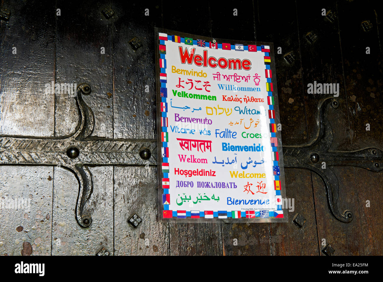 Welcome sign, in many languages, on church door - Stock Image