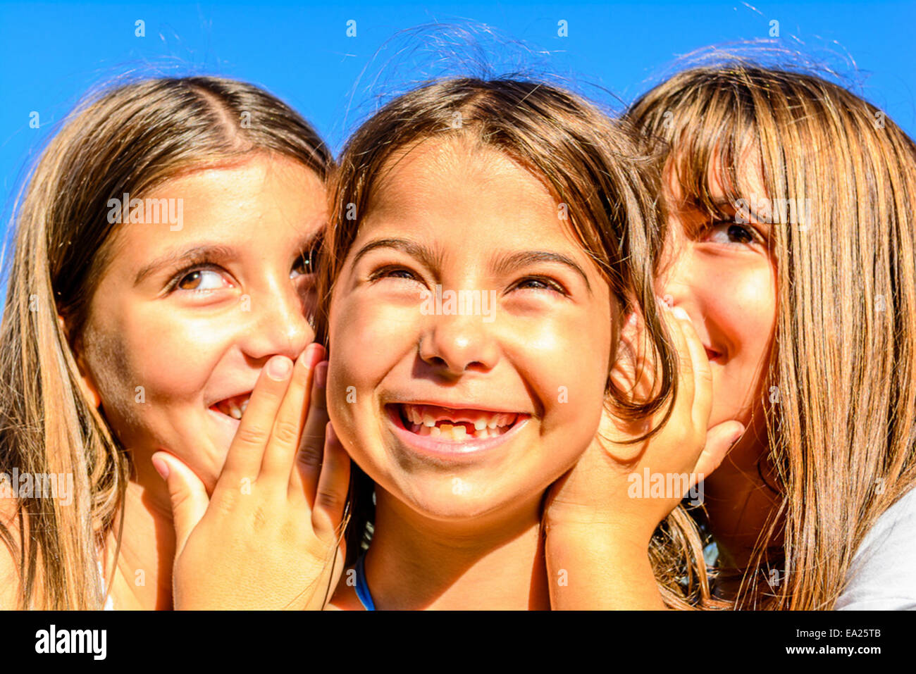 Three little girls are playing and whispering secrets in the park - Stock Image