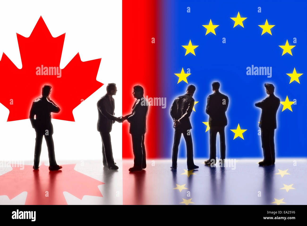 Model figures symbolizing politicians are facing the flags of Canada and the EU. Two of them shake hands. - Stock Image