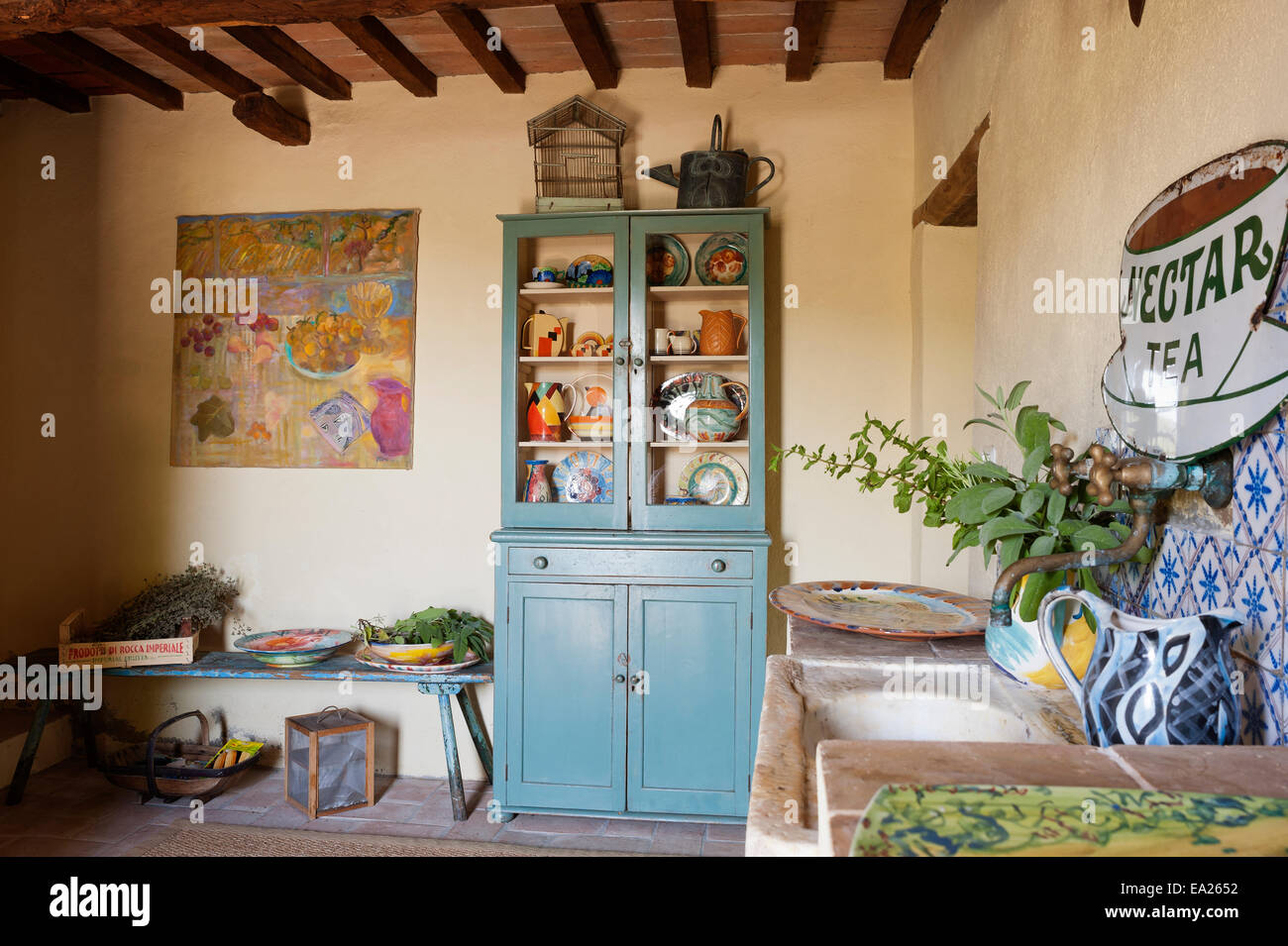 Blue dresser full of brightly coloured crockery and jugs in rustic room with artwork and vintage enamel sign Stock Photo