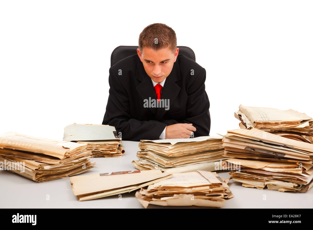 Business man looking at the huge amount of documents on table - Stock Image