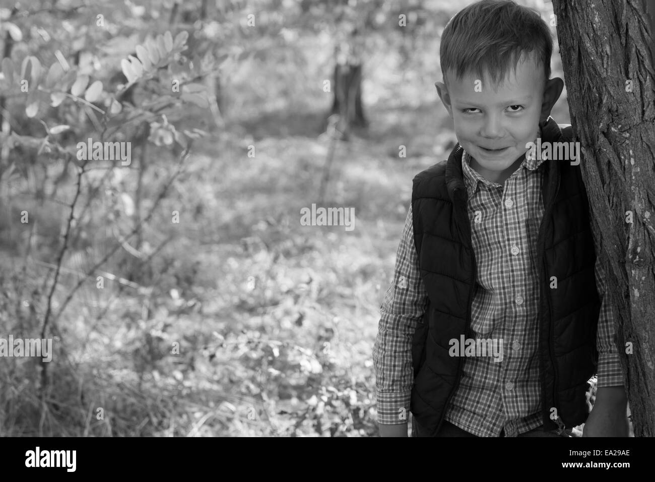 Portrait of Boy with Devilish Grin Outdoors Leaning Against Tree - Stock Image