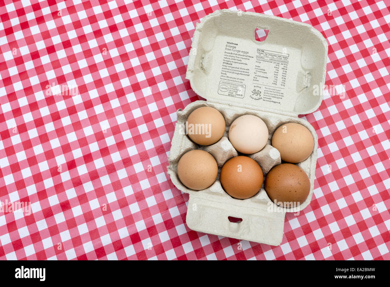 Free range eggs in open egg box on red check tablecloth - Stock Image