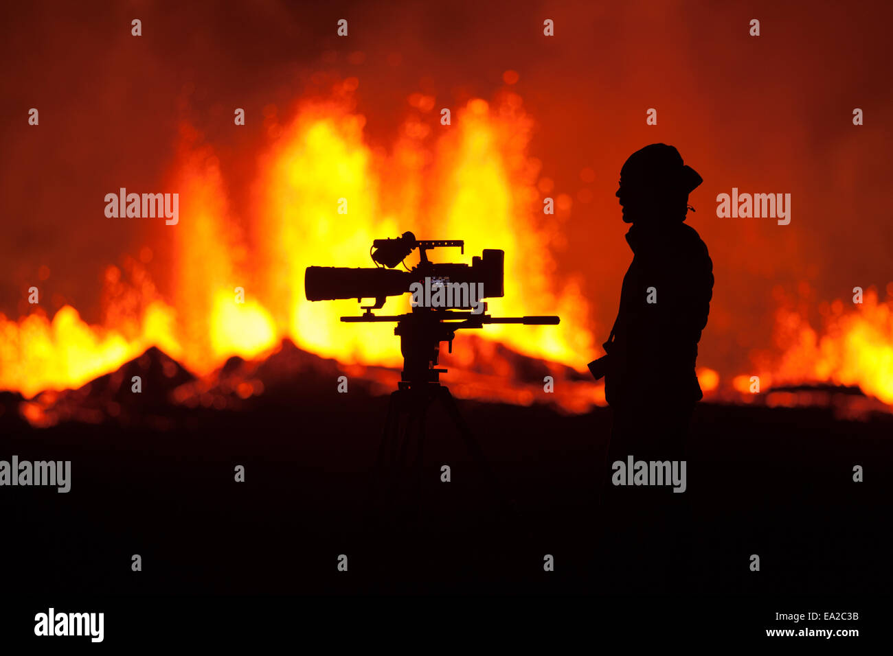 cameraman silhouetted against the iceland eruption - Stock Image