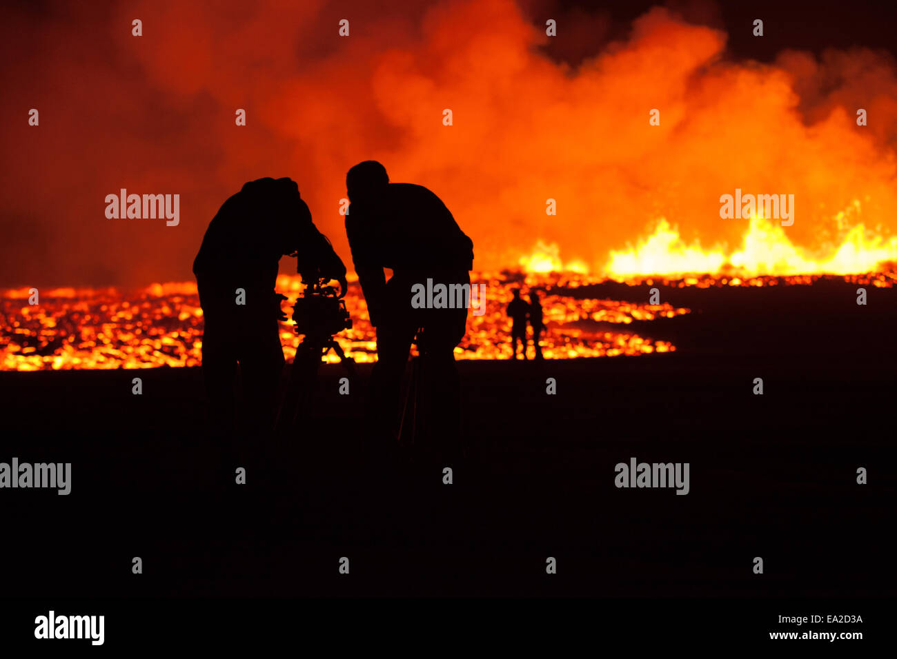 film crew working in front of lava flow - Stock Image