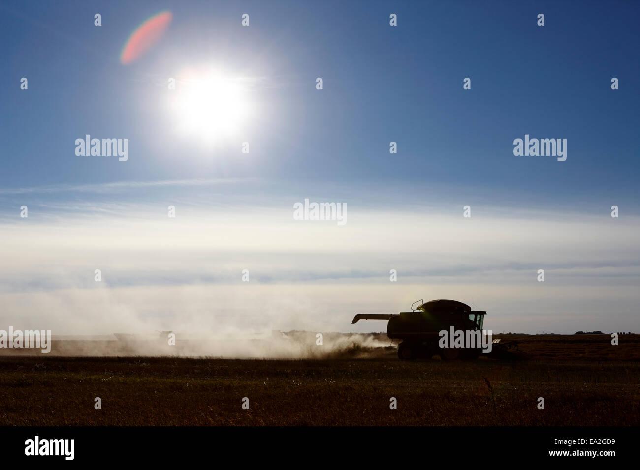 john deere combine harvesters harvesting on the prairies of Saskatchewan Canada - Stock Image