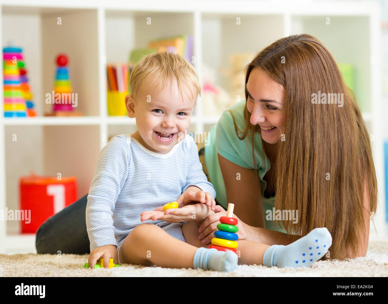 happy mother and child son play together indoor at home - Stock Image