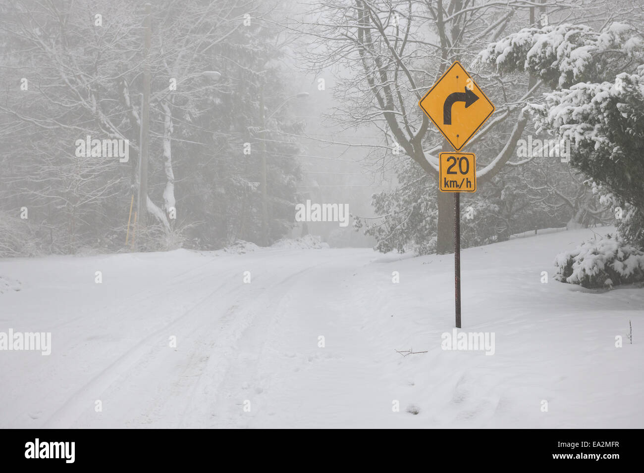 Winter road covered with thick snow and yellow speed limit sign. Toronto, Canada. - Stock Image