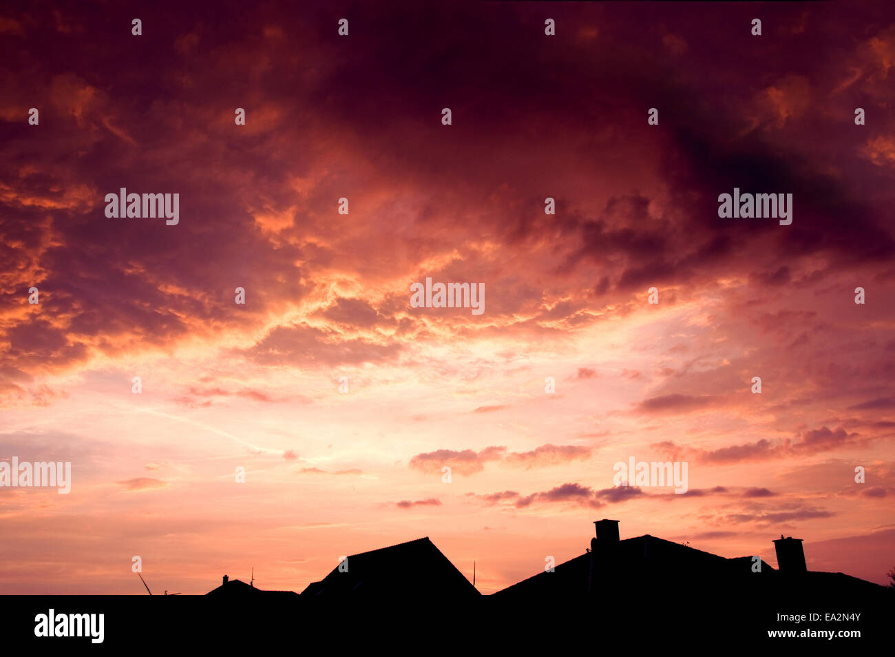 Sunset red sky with dark dramatic clouds over houses. Stock Photo