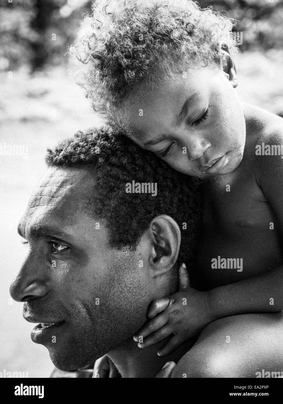Young ni-Vanuatu girl falls asleep while being carried on her father's shoulders - Stock Image