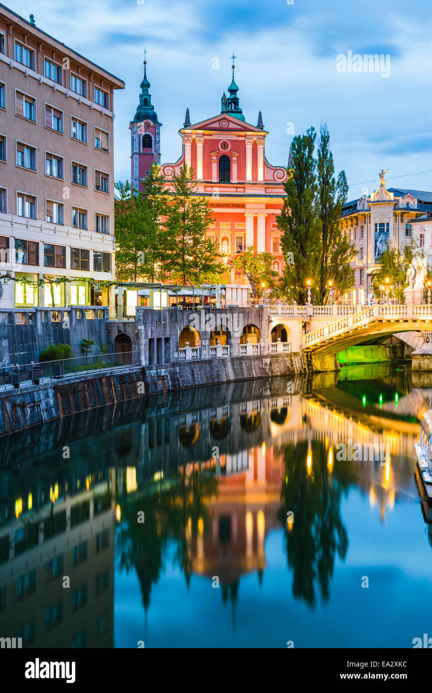 Ljubljana triple bridge and Franciscan Church of the Annunciation reflected in Ljubljanica River at night, Ljubljana, - Stock Image