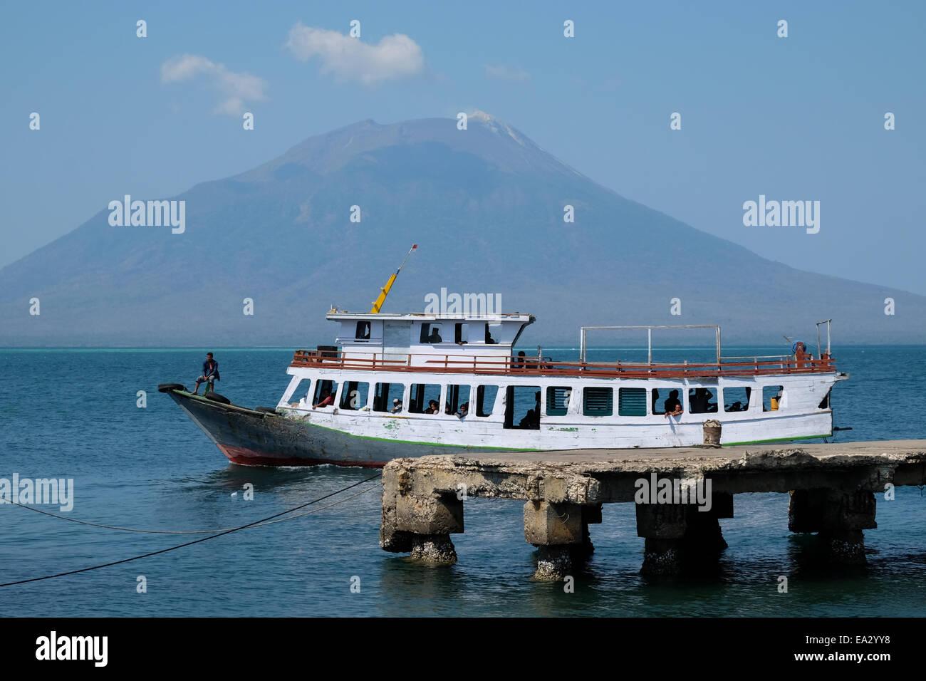 A public transportation boat approaching Lewoleba port, Lembata, East Nusa Tenggara, Indonesia. Mt Lewotolok at - Stock Image