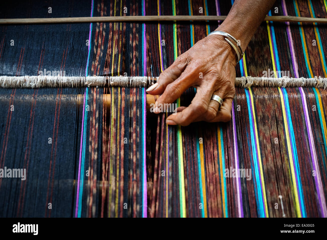 The hand of an old woman weaving traditional fabrics called ikat at her own workshop in Lamagute village, Lembata, - Stock Image