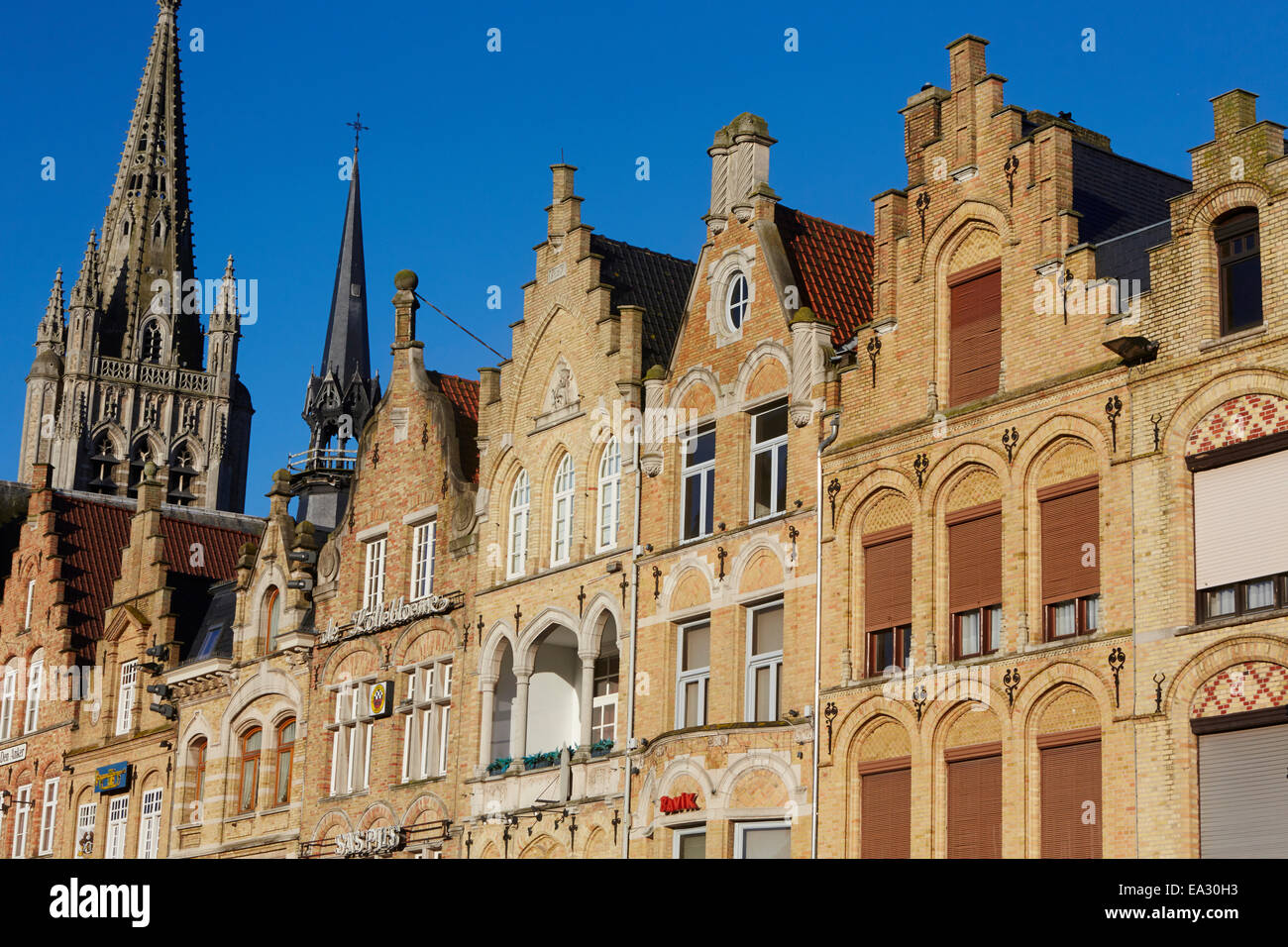 Cathedral spire and Flemish houses in Ypres, West Flanders, Belgium, Europe - Stock Image