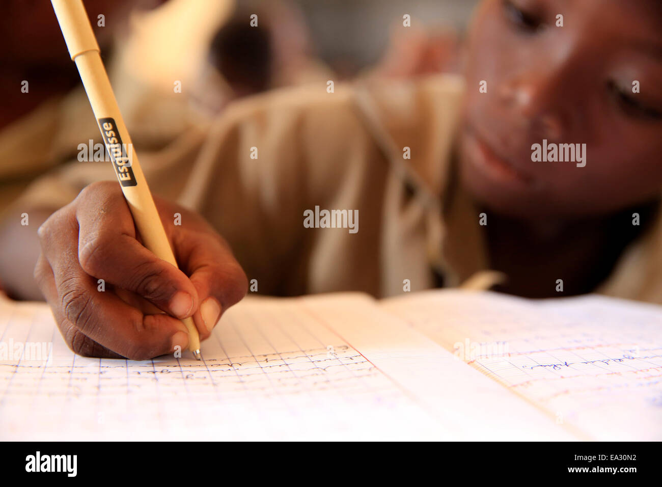 Pupil taking notes in French class in African primary school, Lome, Togo, West Africa, Africa - Stock Image
