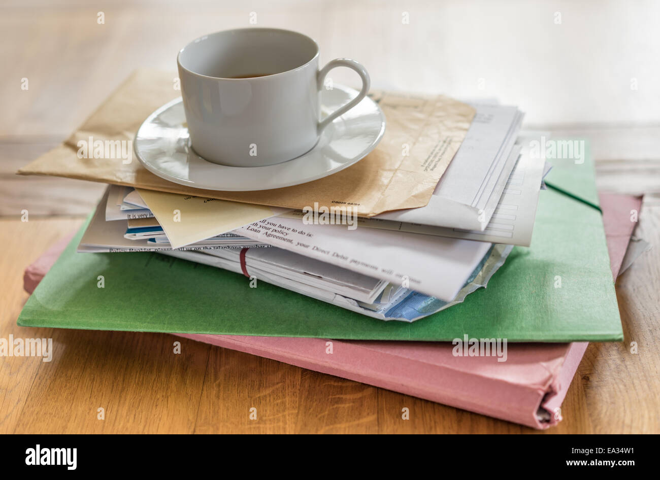 Cup of coffee balancing on a pile of bills - Stock Image