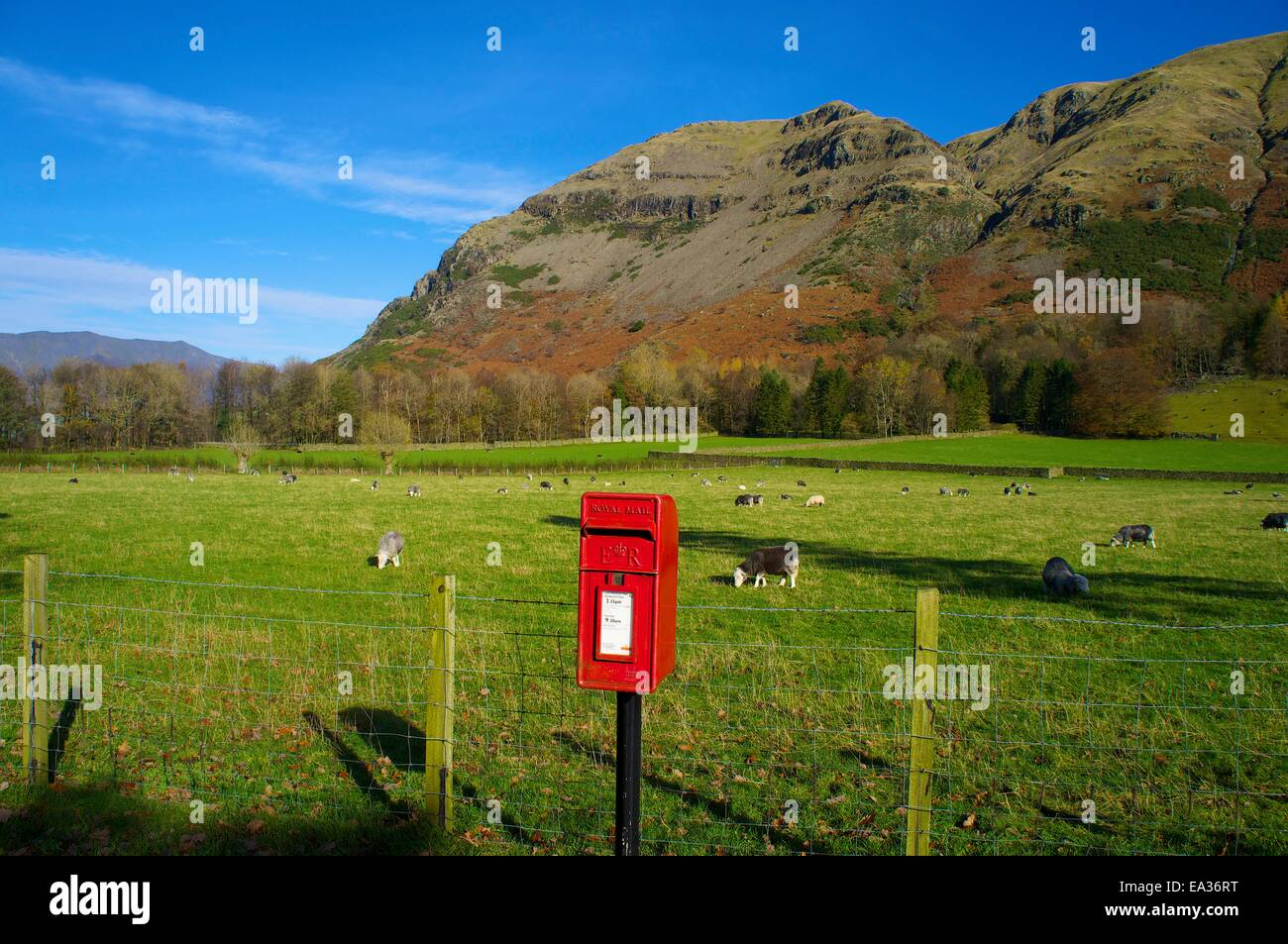 Red post box on a pole in St. John's in the Vale, Lake District National Park, Cumbria, England, UK. - Stock Image