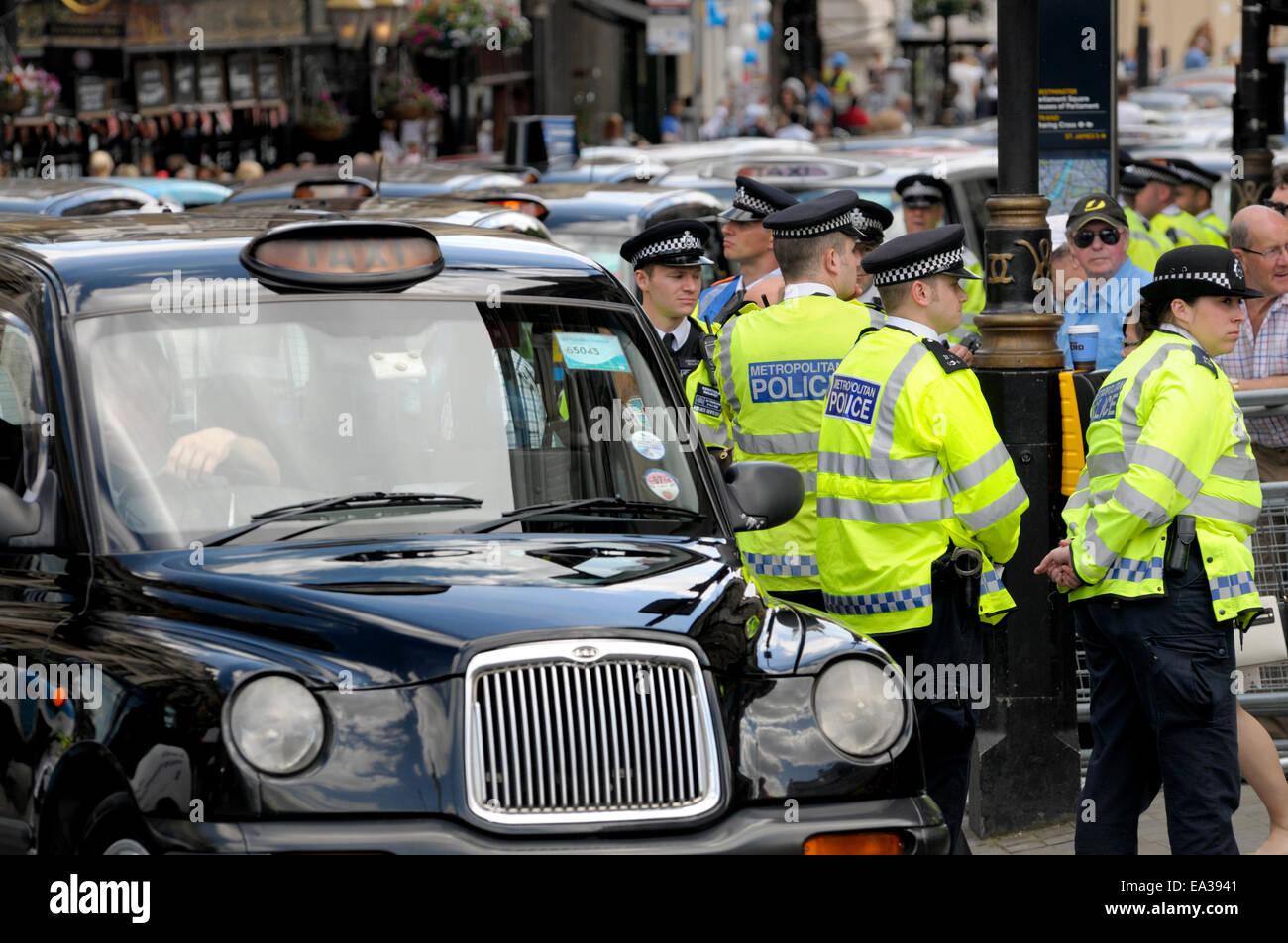 London, England, UK. Metropolitan police officers and London Black cab drivers blockading Trafalgar Square in demo - Stock Image