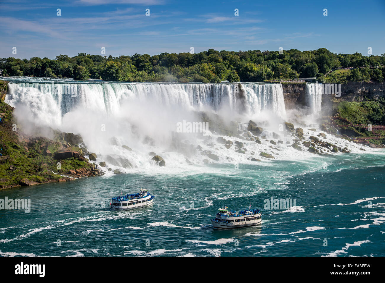 The American Falls with two tour boats at it's base as seen from Niagara Falls Canada. - Stock Image