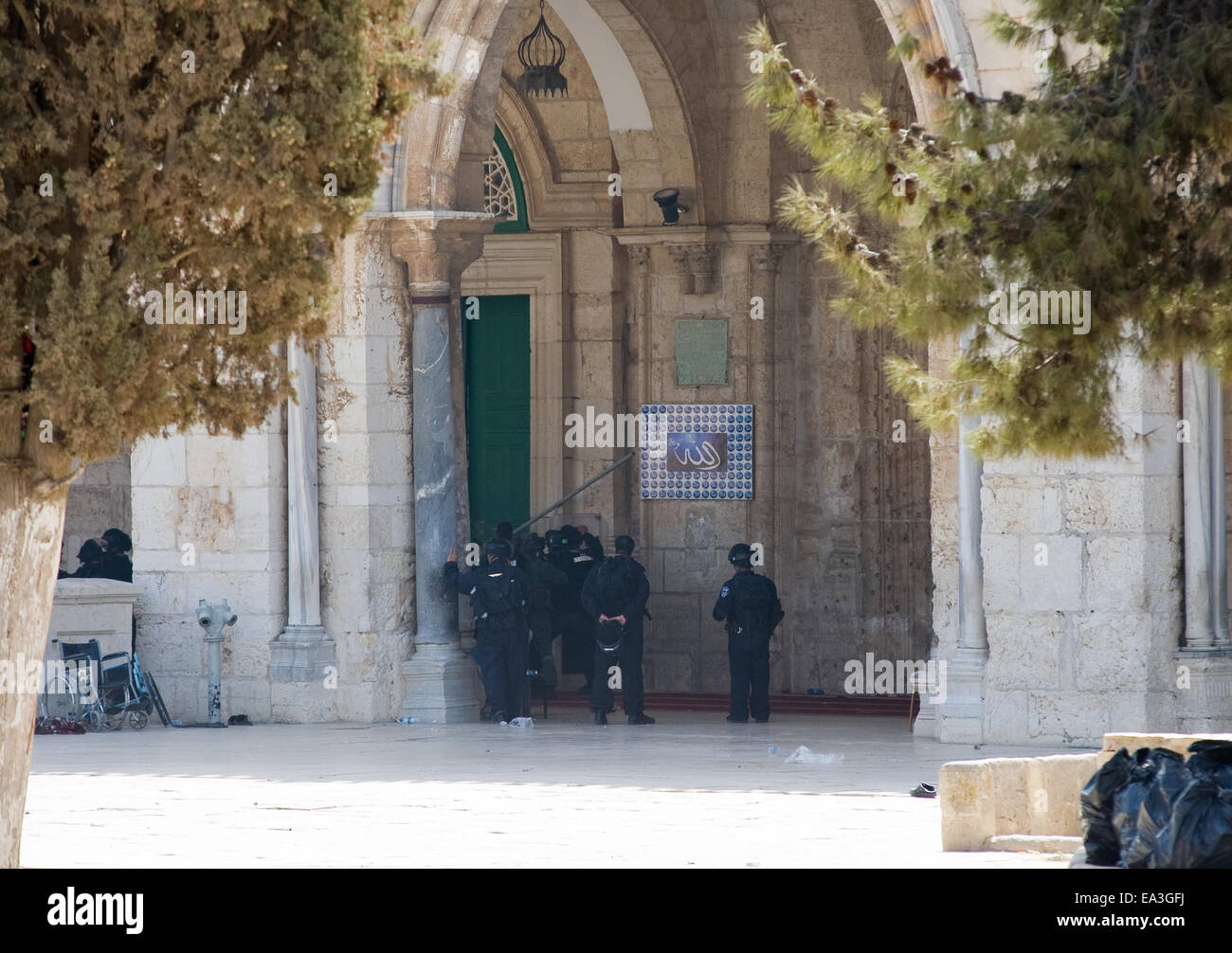 Israeli security officers with an iron bar try to open a door of the main entrance of the Al-aqsa mosque in Jerusalem - Stock Image