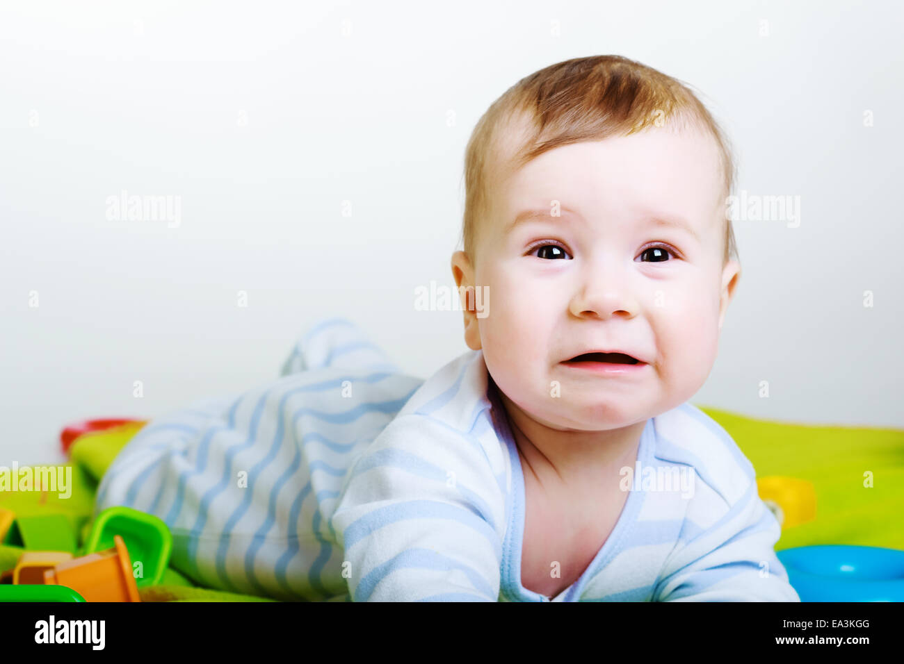 Little baby boy with toys weeps - Stock Image
