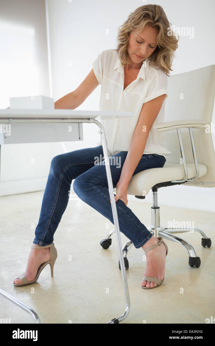 Casual businesswoman touching her ankle - Stock Image