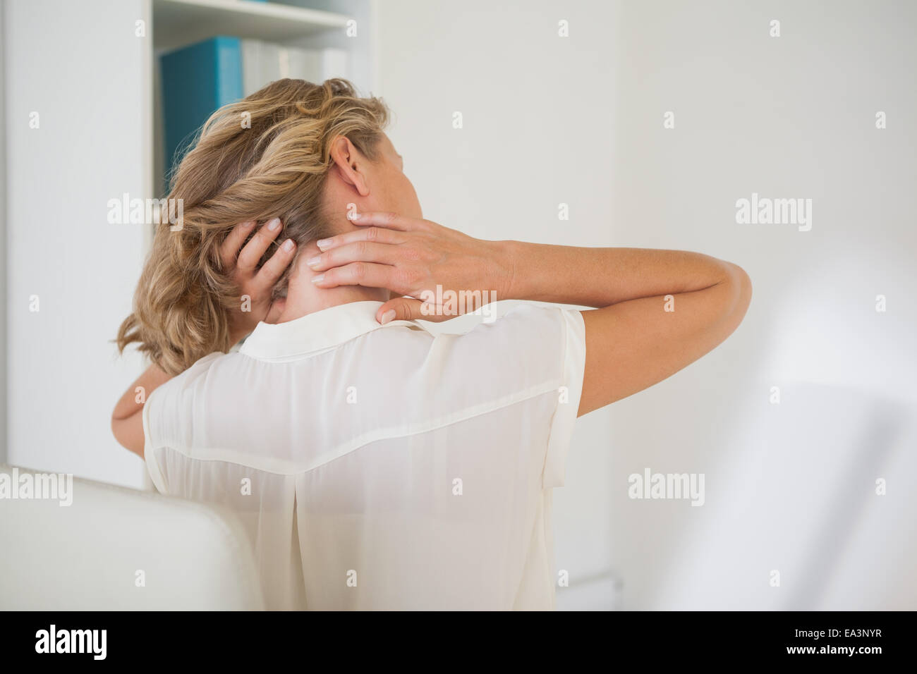 Casual businesswoman rubbing her neck - Stock Image