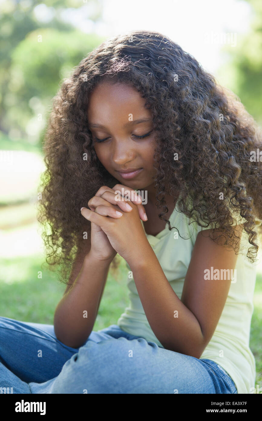 Young girl praying in the park - Stock Image