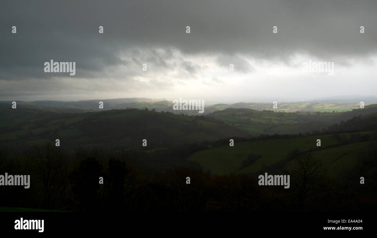 Carmarthenshire, Wales, UK. 6th November, 2014.  Dark clouds with glimmers of sunlight over Llandovery on an autumn - Stock Image