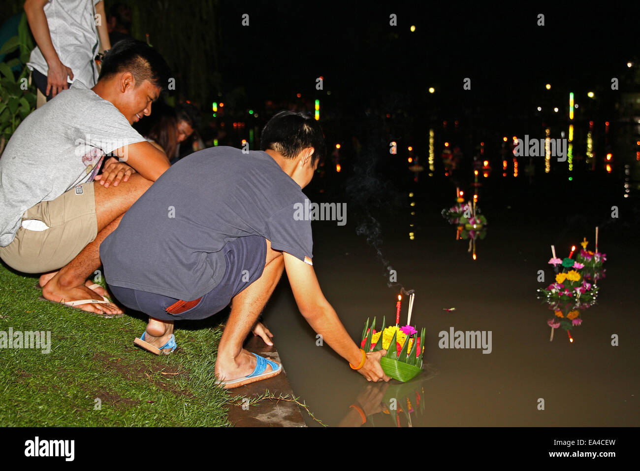 Chatuchak Park's lake, Bangkok, Thailand. 6th November 2014. A young man places his krathong (small vessel) in the Stock Photo
