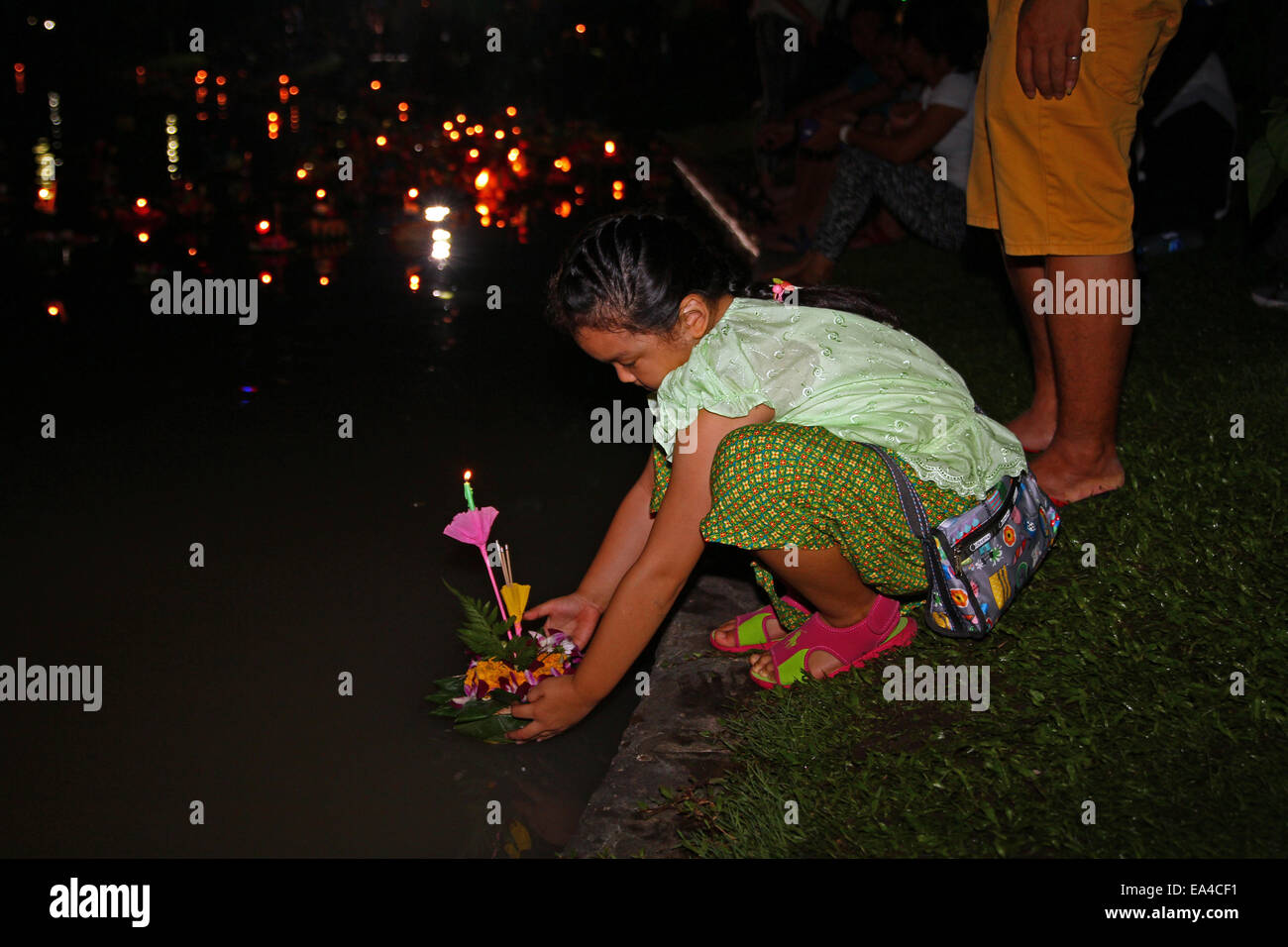 Chatuchak Park's lake, Bangkok, Thailand. 6th November 2014. A little girl places her krathong (small vessel) in Stock Photo