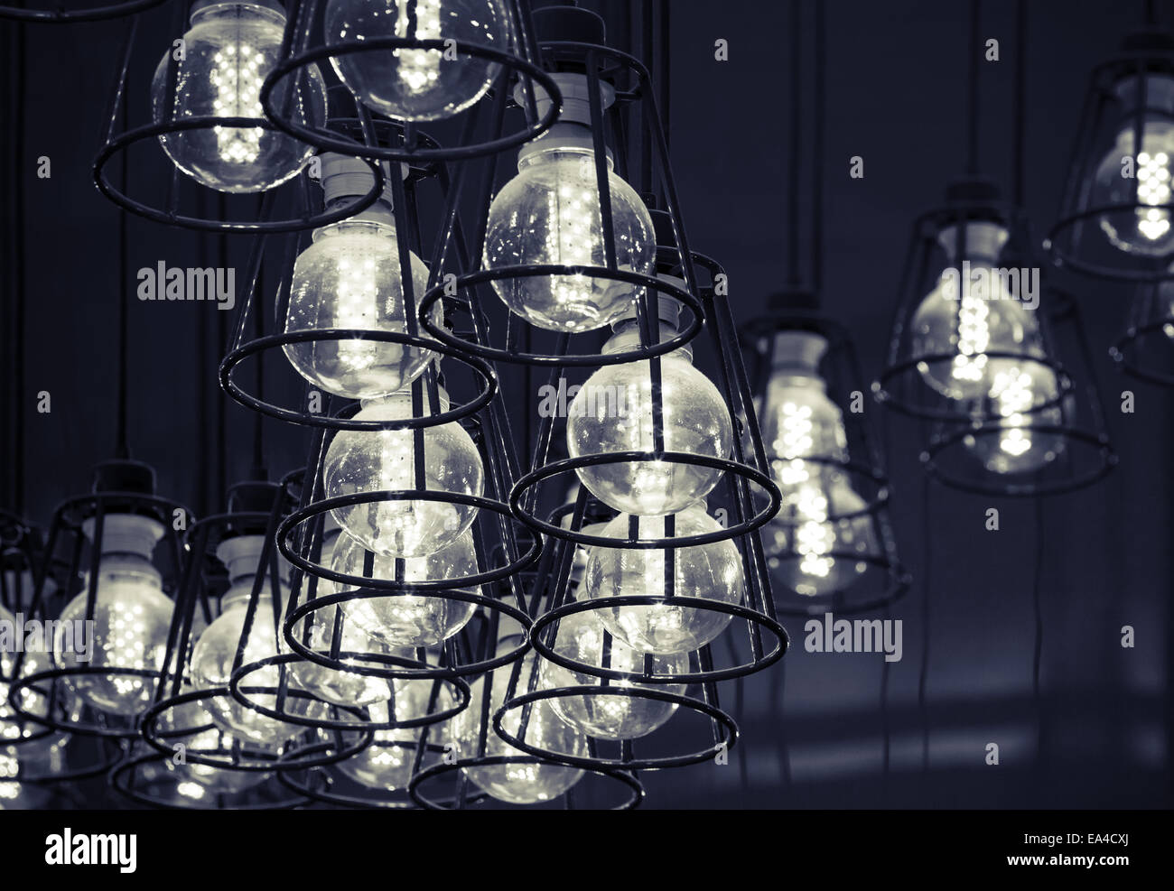 Abstract interior fragment. Stylized vintage illumination with modern LED lamps in metal lampshades, black and white - Stock Image