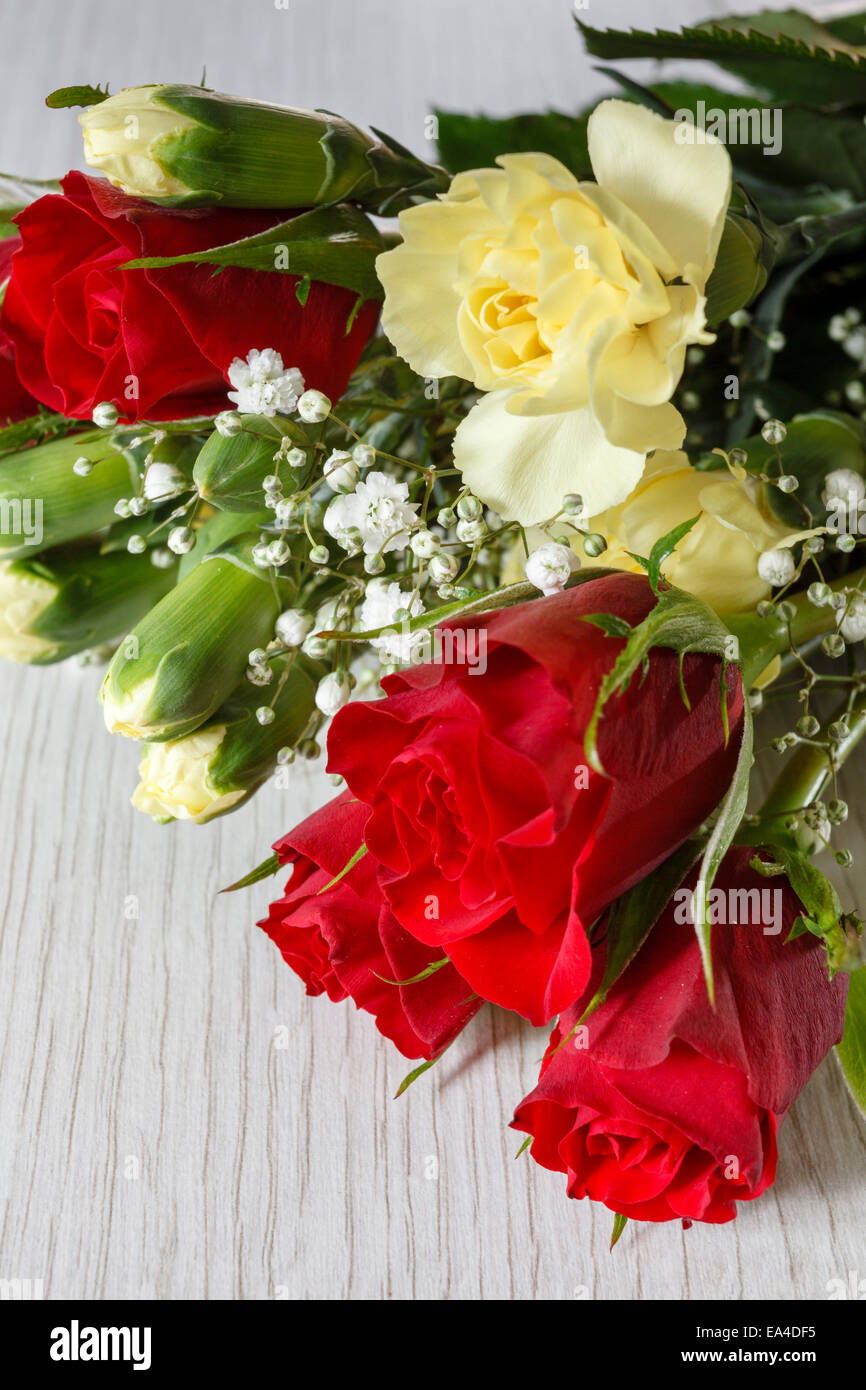 Bunch of mixed cut flowers, mainly red roses - Stock Image