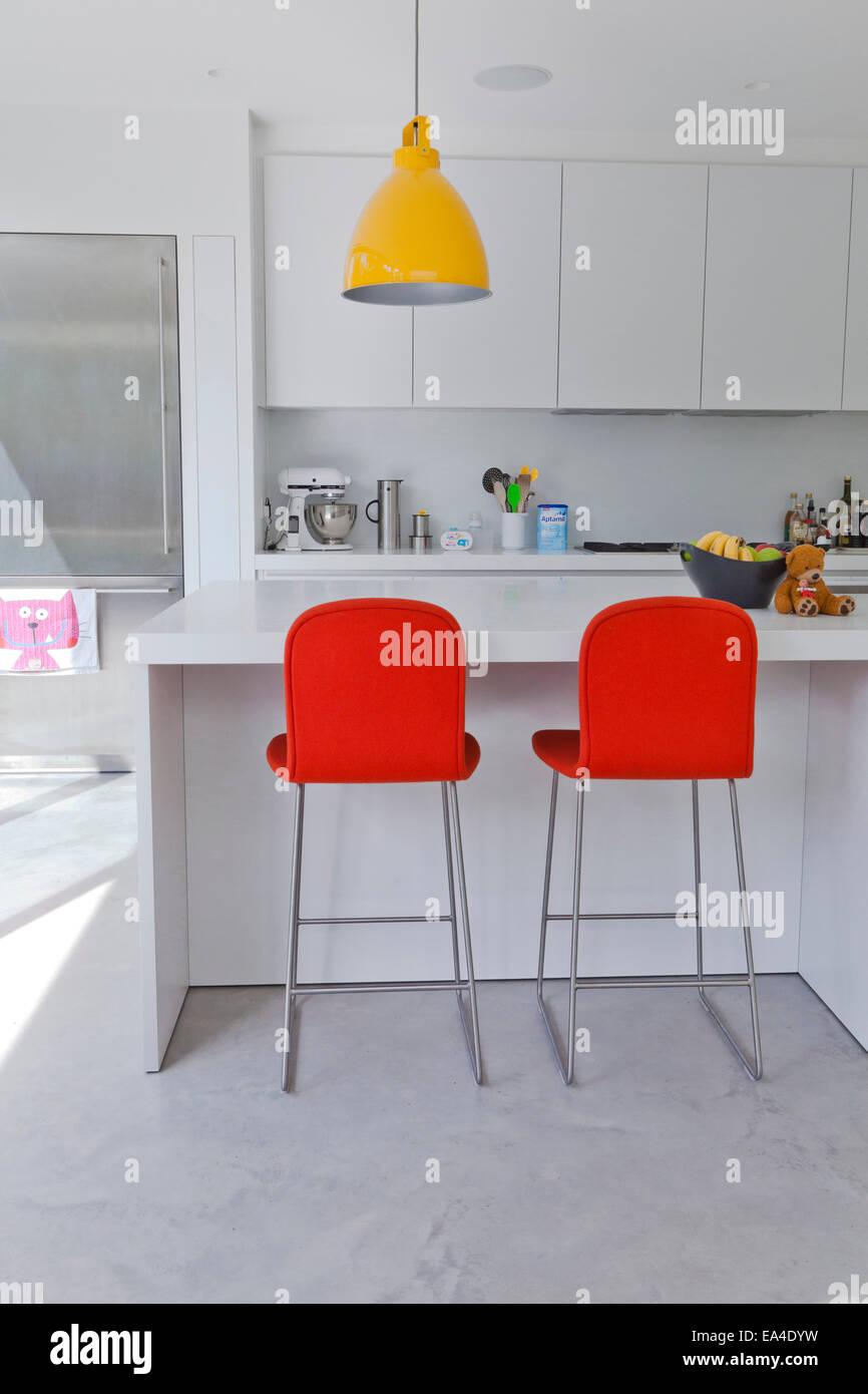 Orange bar stools in white kitchen of London home, UK Stock ...