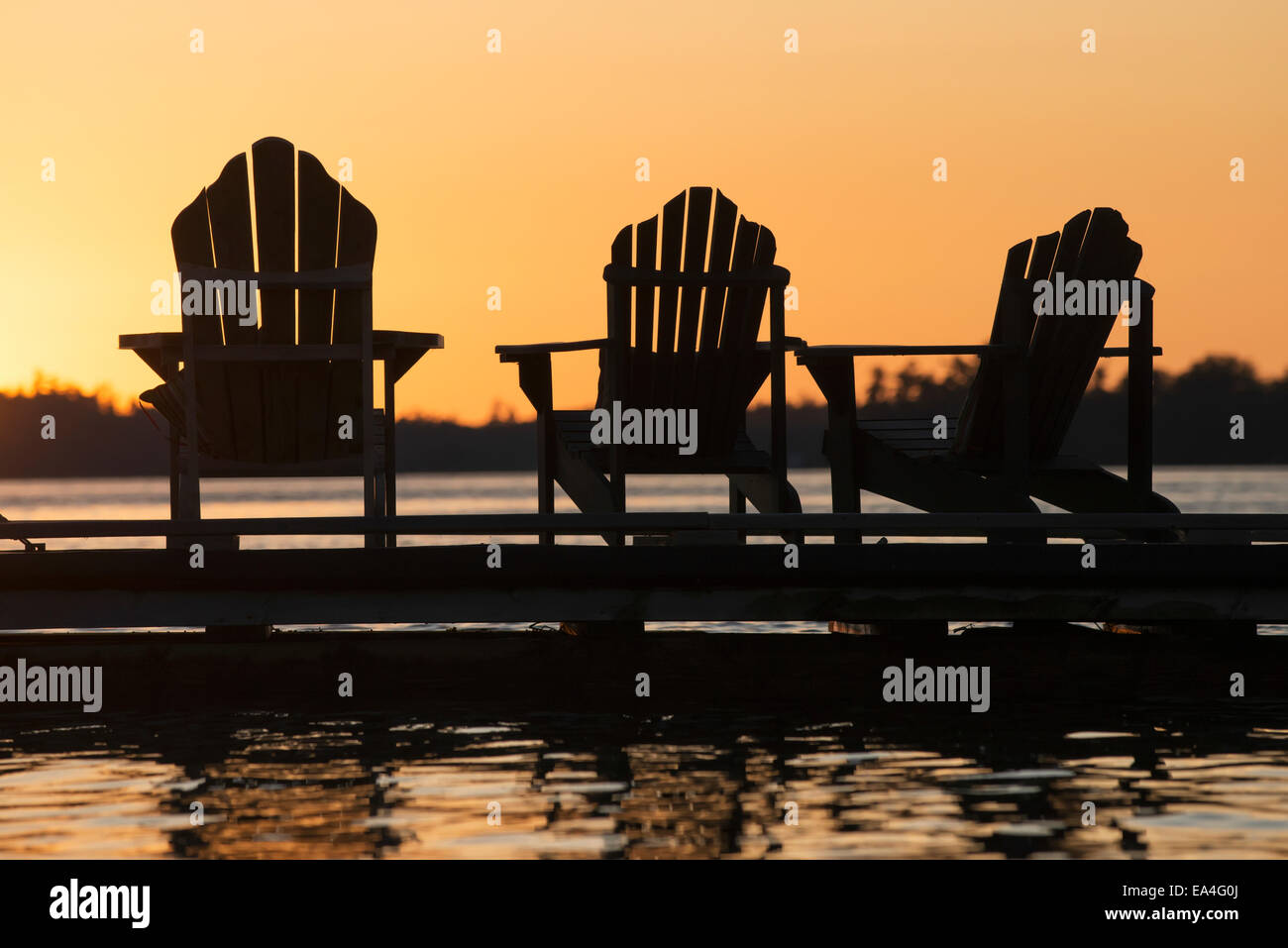 Silhouette of three adirondack chairs on a dock at sunset Ontario