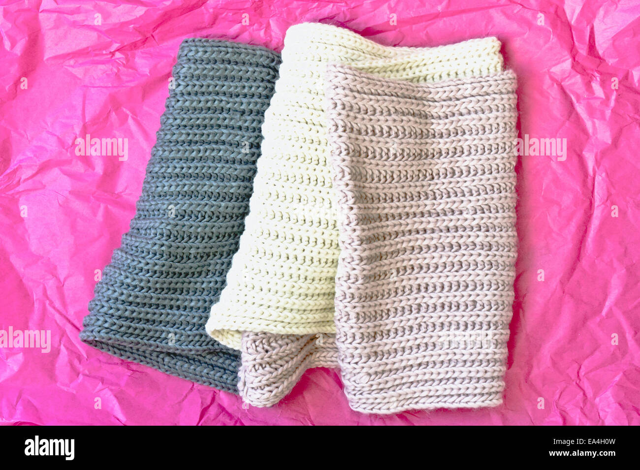 A folded wool scarf on a piece of pink tissue paper - Stock Image