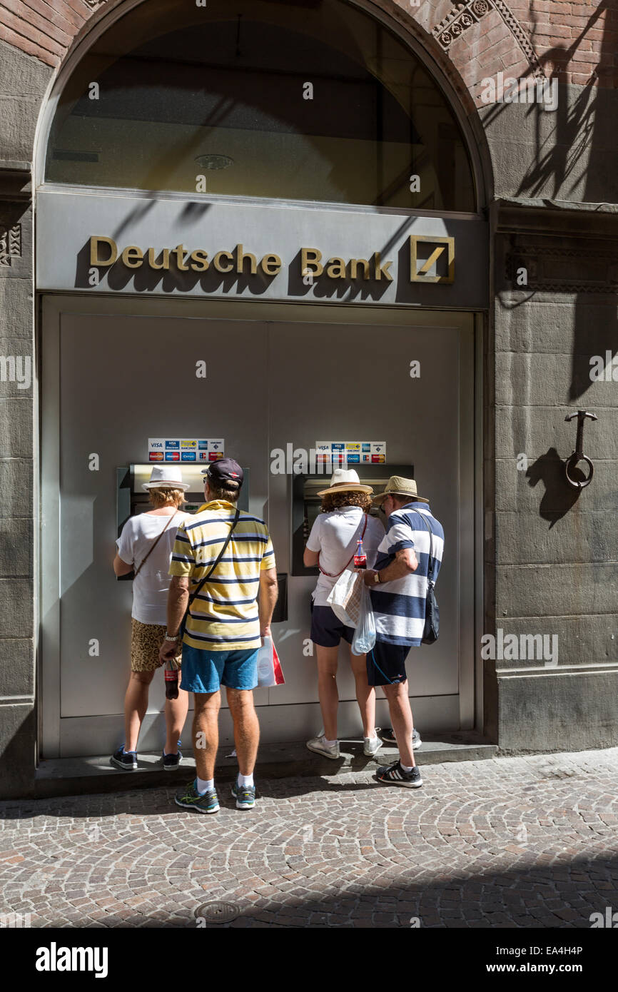 Four tourist withdrawn cash from an ATM, Deutsche Bank cashpoint - Stock Image