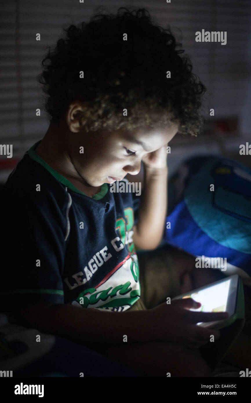 mixed race boy playing games and learning on an ipad type device with light lighting up their faces in the dark. - Stock Image
