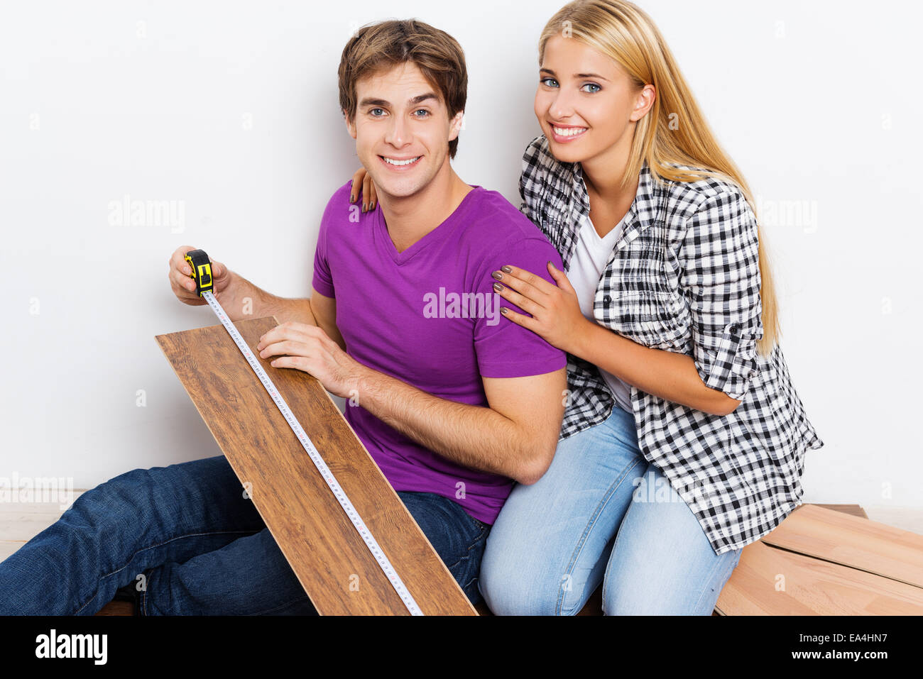 Young couple measuring woodblock - Stock Image