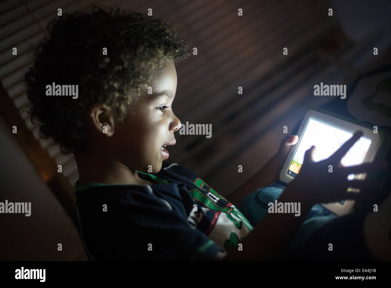 mixed race child playing games and learning on an ipad type device with light lighting up their faces in the dark. - Stock Image