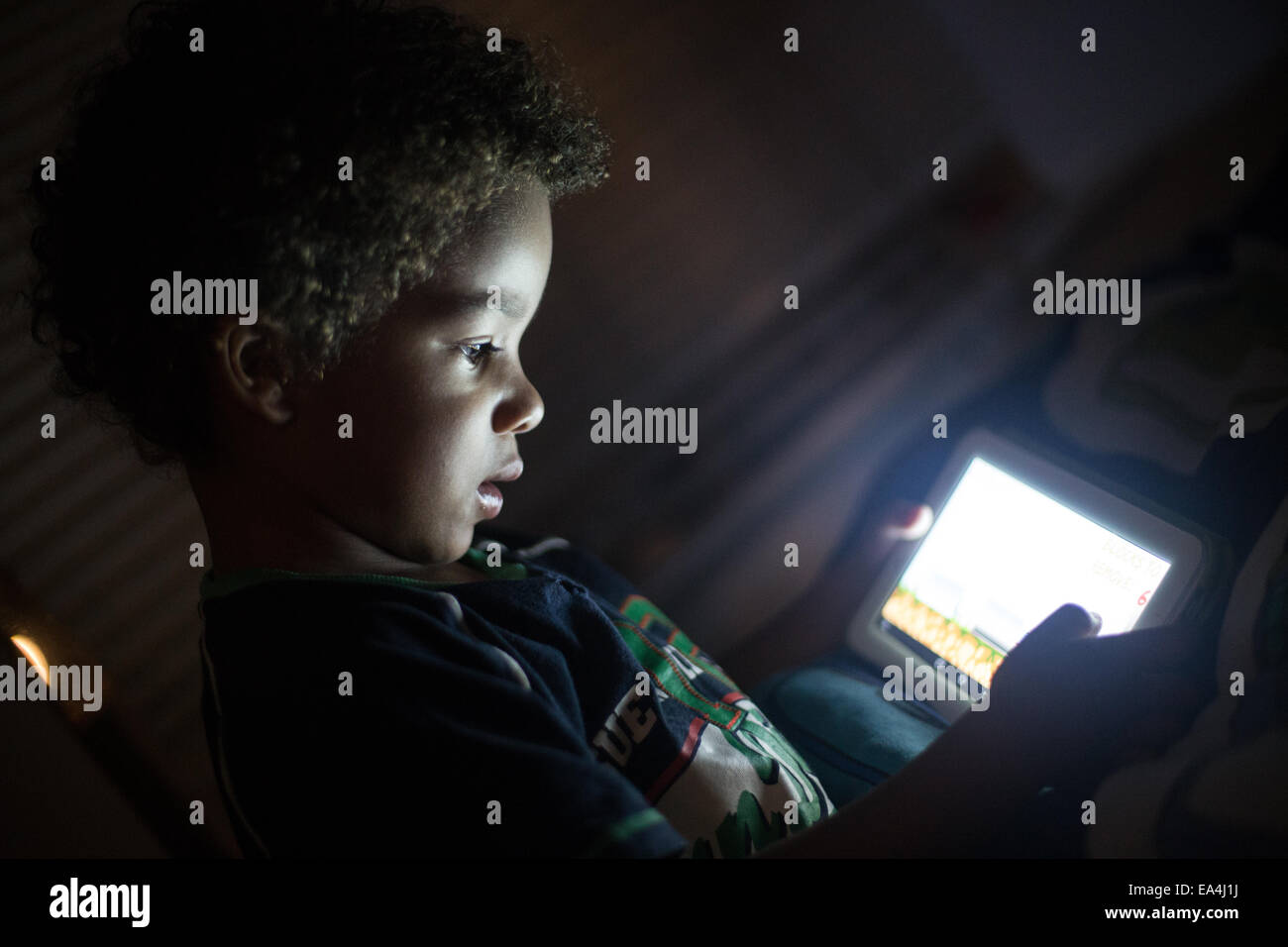 mixed race child playing games and learning on an ipad type device with light lighting up his face in the dark. - Stock Image