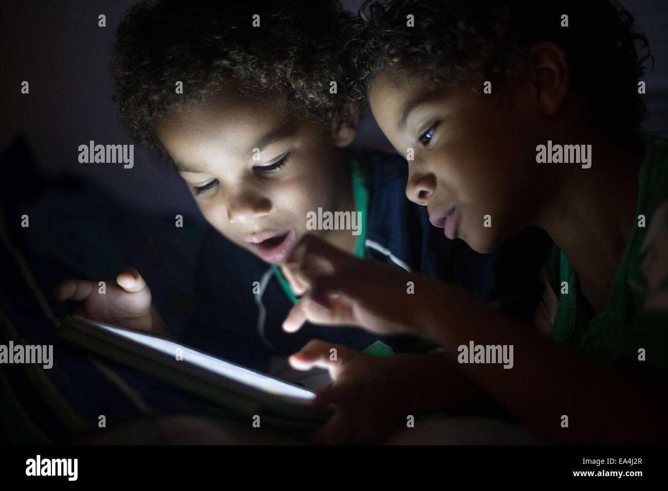 mixed race brothers playing games and learning on an ipad type device with light lighting up their faces in the - Stock Image