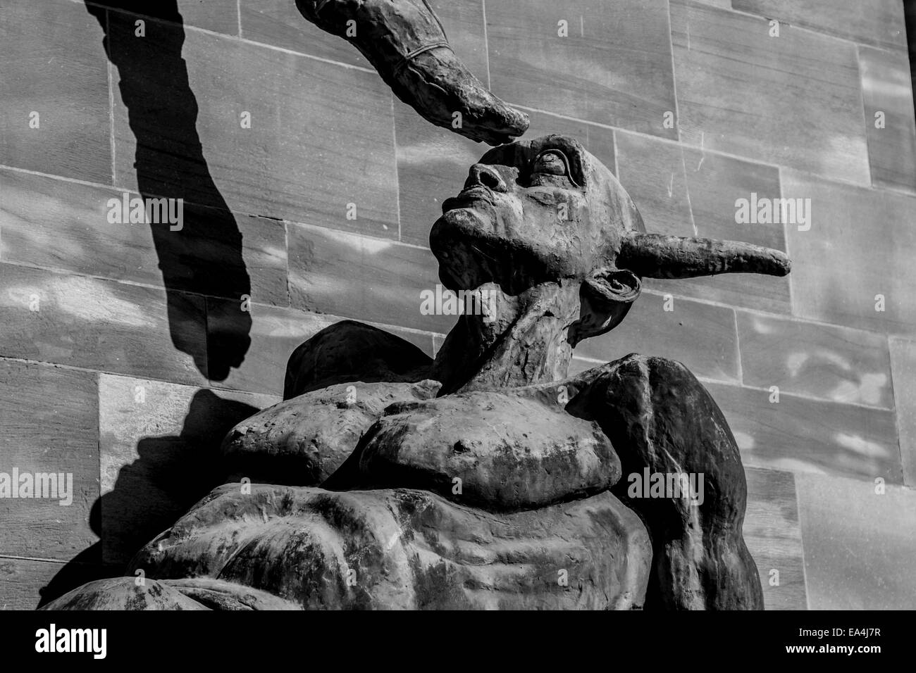 Statue of St Michael Subduing the Devil by Sir Jacob Epstein on the wall of the Cathedral in Coventry Britain - Stock Image